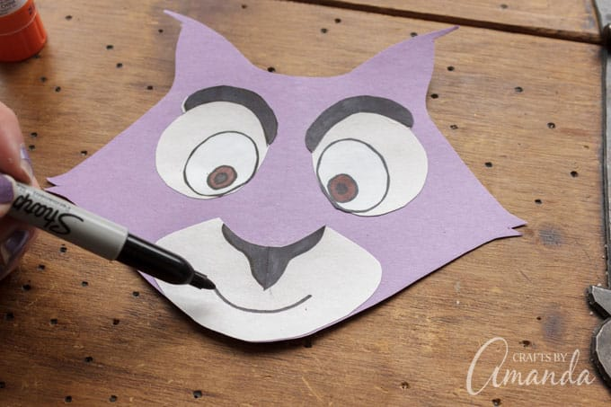 Glue the pieces to the face, then glue the completed face to the bottom flap of the paper bag.