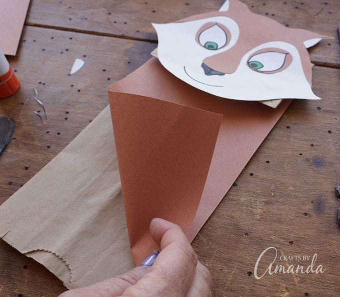 To finish off the puppets, cover the front of the bags with brown paper (Andie) and purple paper (Surly) and a strip of white paper for the belly fur.