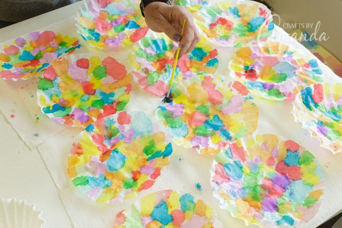 Place coffee filters onto the paper towels and paint with watercolors.
