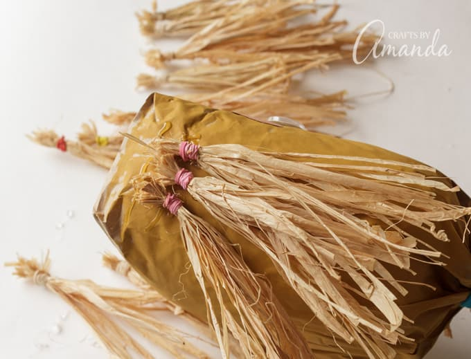Using raffia as hair for a paper bag scarecrow