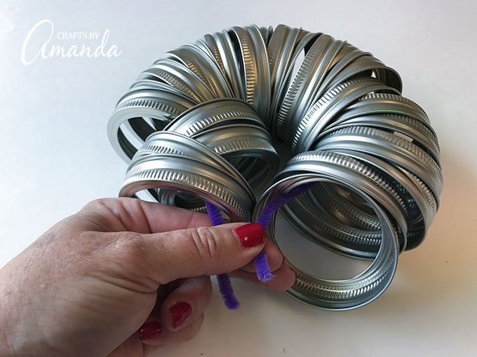 Tying mason jar lid bands together with a pipe cleaner.