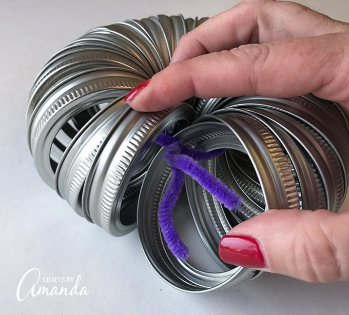 Tying mason jar lids together with pipe cleaner