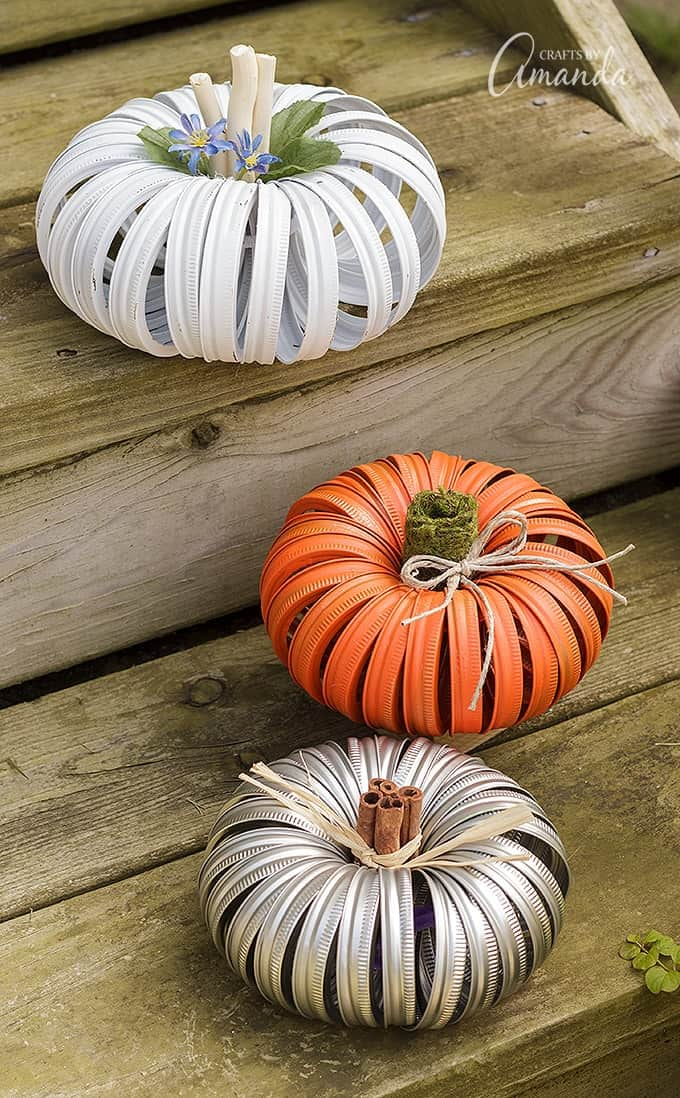 Pumpkins made out of canning lids from mason jars sitting stairs