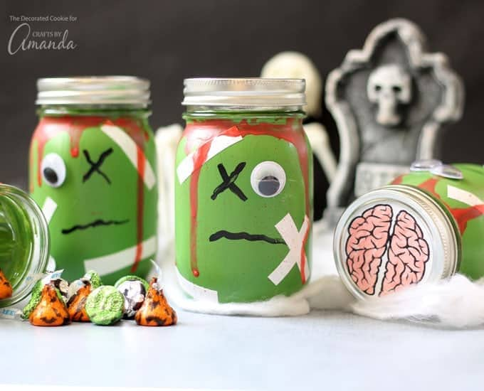 Mason jars decorated as zombies for Halloween filled with candy