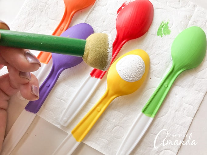 Using a spouncer to make eyeballs on plastic spoons