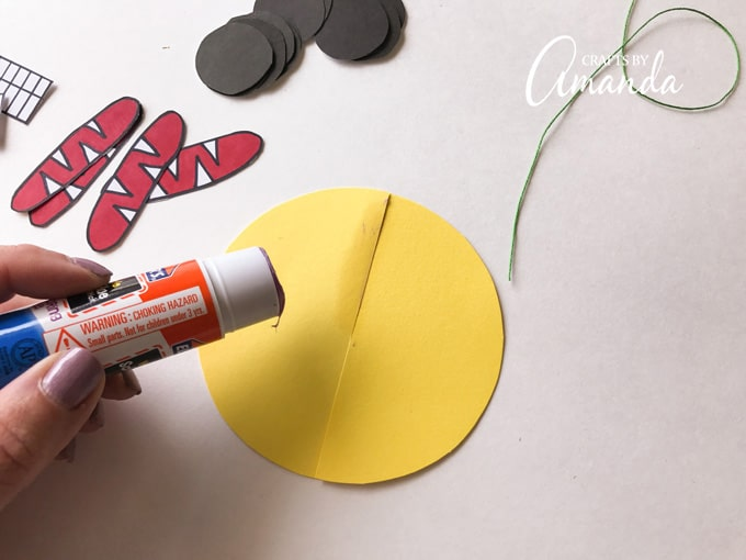 Using a glue stick, apply a strip of glue along one of the slits.