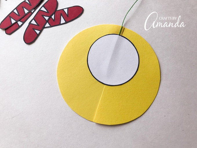 Next use the glue stick to attach a medium circle to the large circle, covering the string.