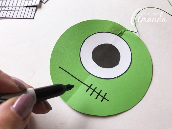 Make a stitched mouth by drawing a horizontal line across the circle then drawing vertical lines 1/4-inch apart.