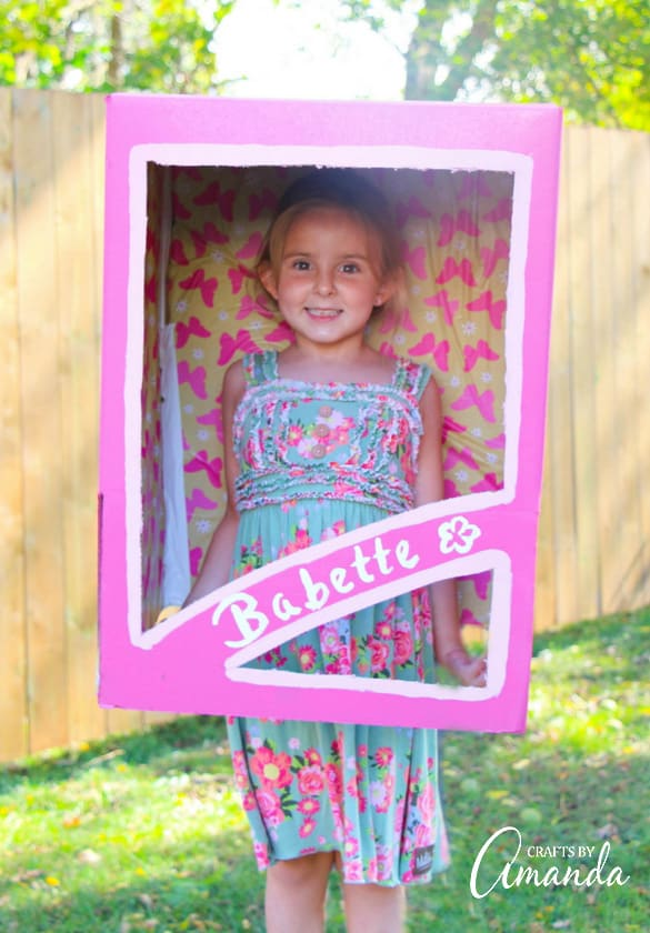 girl standing inside a pink doll box costume