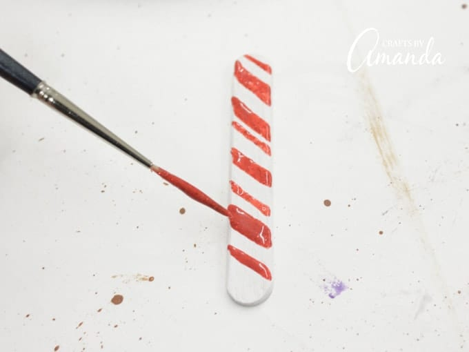 Use a liner brush dipped in Red Rocket glitter paint to add diagonal lines onto 4 of the 5 white sticks.