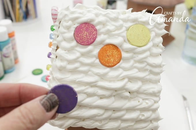 Now that the wood circles are dry, gently press them into the Collage Clay on the roof.
