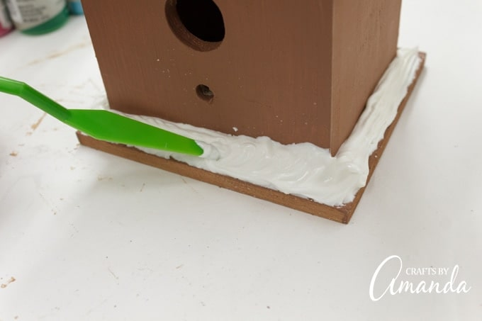 Spread Collage Clay along the bottom of the birdhouse and insert candies.