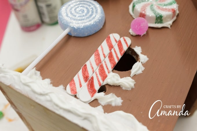 "Make sure the peppermint craft sticks are dry, then attach them to the front of the house as the door, lining them up next to each other above the ""step"" stick."