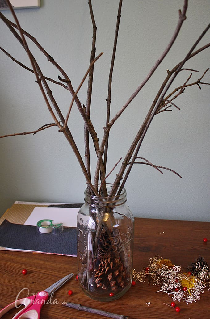 Drop a couple of large pinecones into the jar. Arrange branches in the jar until you are happy with how it looks.