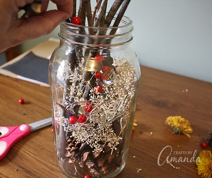 ​Fill gaps in between the pinecones and branches by dropping faux berries and dried florals into the jar.