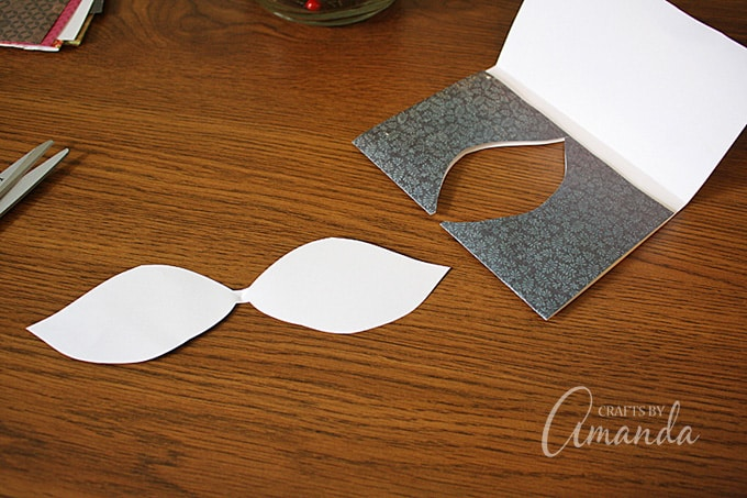 Fold scrapbook paper in half. Beginning at the folded edge, cut out a simple leaf shape, creating a small tab at the fold to hang the leaf from.