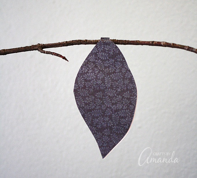 """Place the """"tab"""" of the leaf on the branch and stick the two sides of the leaf together with the tape."""