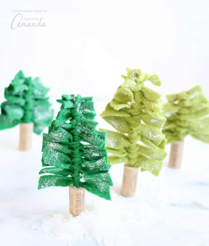 These felt Christmas tree centerpieces are an easy-to-make DIY holiday decoration. Create a forest of Christmas trees for your holiday table, or decorate your fireplace mantle or shelves. You can even use them individually as gift toppers.