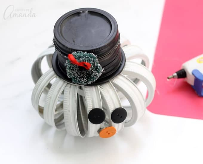 Mason Jar Lid Snowman gluing on accessories