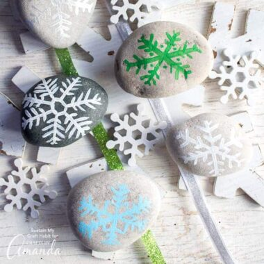 Add a fun little accent to your holiday decor with these painted rock snowflakes. Grab the template for this simple and relaxing rock painting craft.