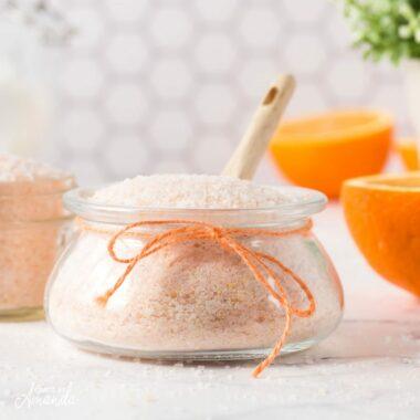 orange bath salts in a jar with a spoon