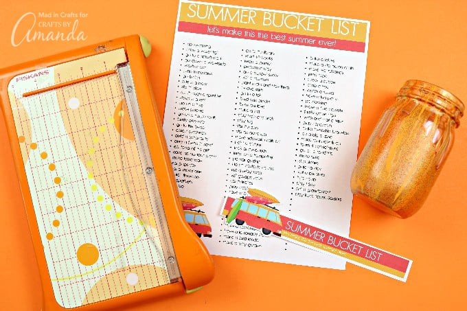 using a paper cutter to cut bucket list then put in jar on orange background