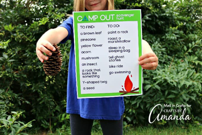 girl holding pine cone and scavenger hunt sheet