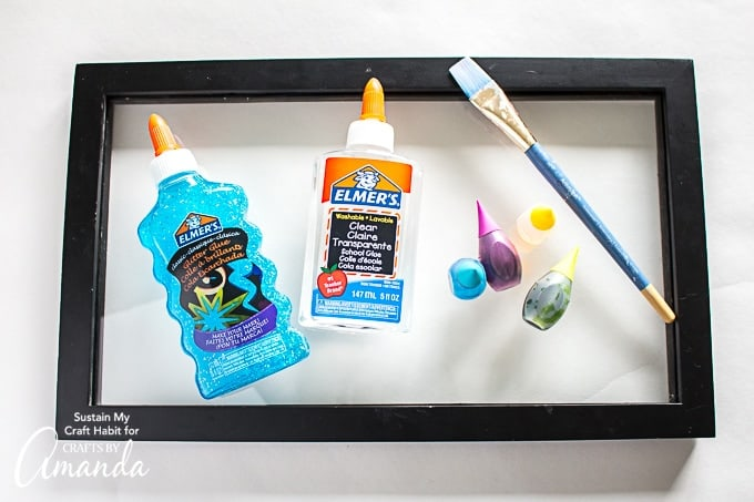 Glue, glitter glue, food coloring, and a paint brush in a frame for DIY stained glass.