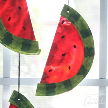 Watermelon suncatchers are a fun summer craft kids can make with adults. This suncatcher is made from paper plates, paint, and melted crayons!
