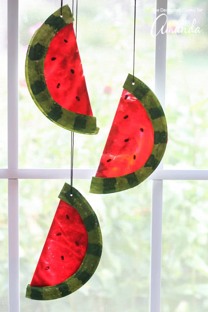 Watermelon Suncatchers hanging in a window from a string