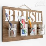 Organize your bathroom with this mason jar bathroom organizer for toothbrushes. Using vinyl and a cutting machine this project comes together quickly!