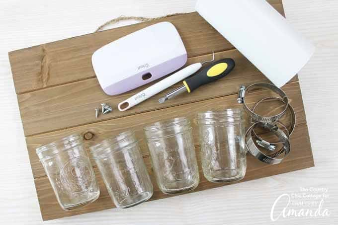 Mason Jars, cutting machine, and a wood sign to make mason jar bathroom organizer
