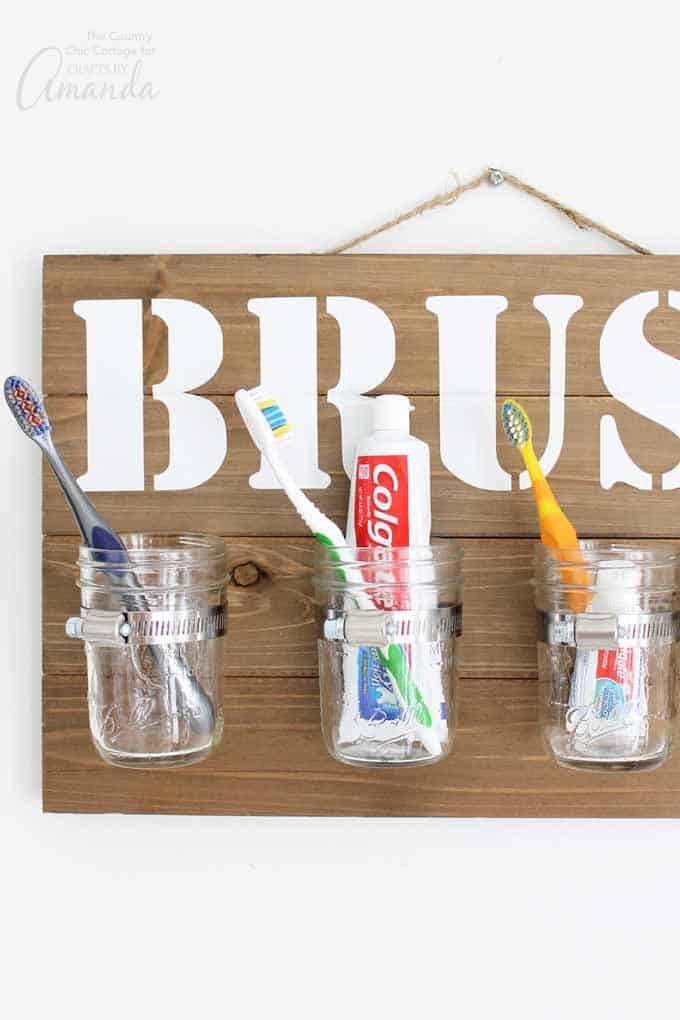Sign holding mason jars with toothbrushes inside