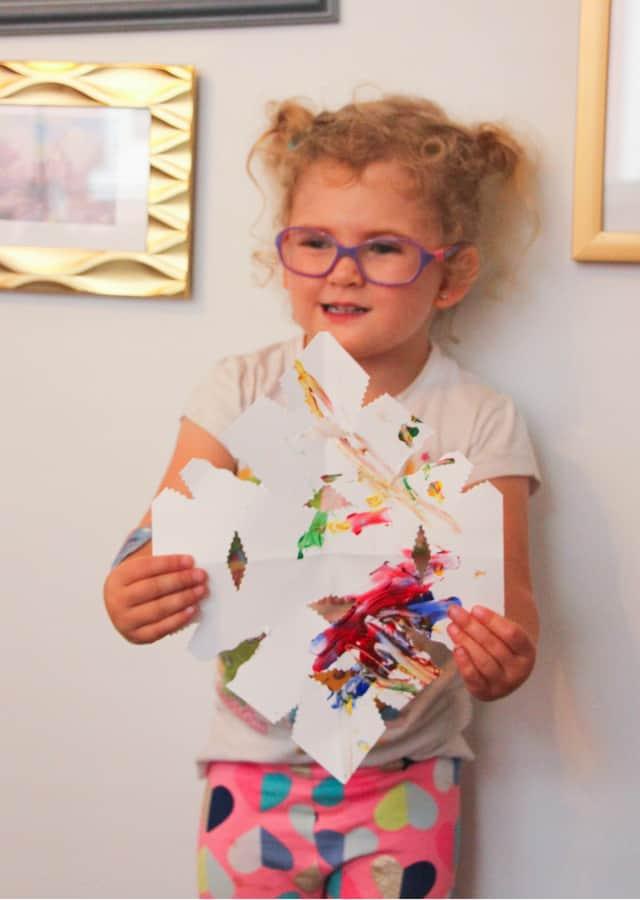 toddler holding paper snowflake
