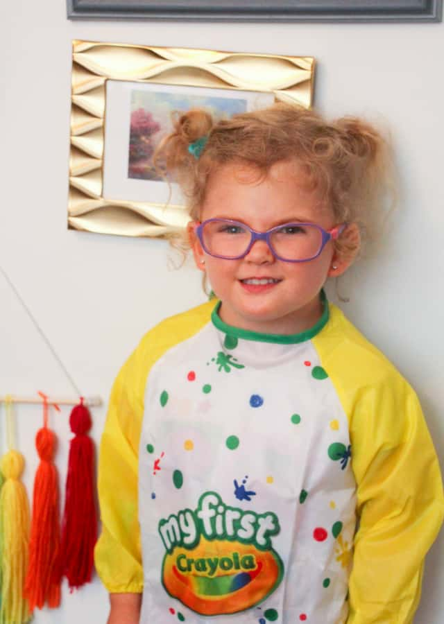 toddler smiling wearing smock