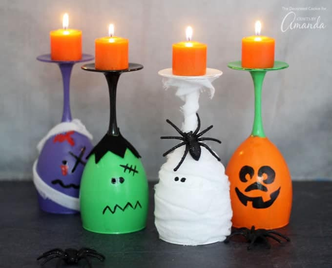 Wine glasses painted as a zombie, Frankenstein, a mummy, and a pumpkin with candles on top!