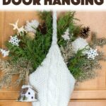 Create your own beautiful door hanging using some foraged greens, a knitted hat and some additional Winter-themed decor picks. #winter #wintercrafts #diy #christmasdecor #christmascrafts #adultcrafts #homedecor #diyhomedecor #easycrafts #hotglue