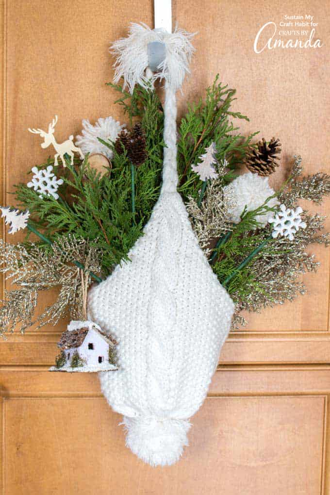 door hanging made out of a winter hat and greenery