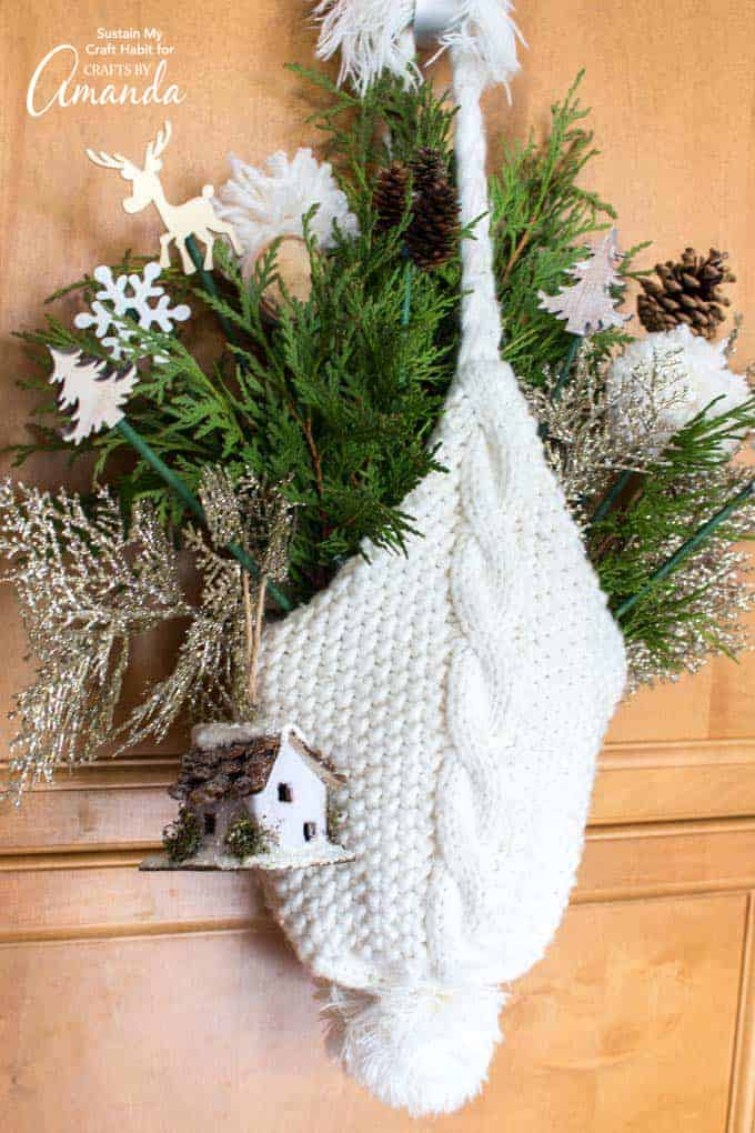 winter hat door hanging made from a knitted hat and winter greenery
