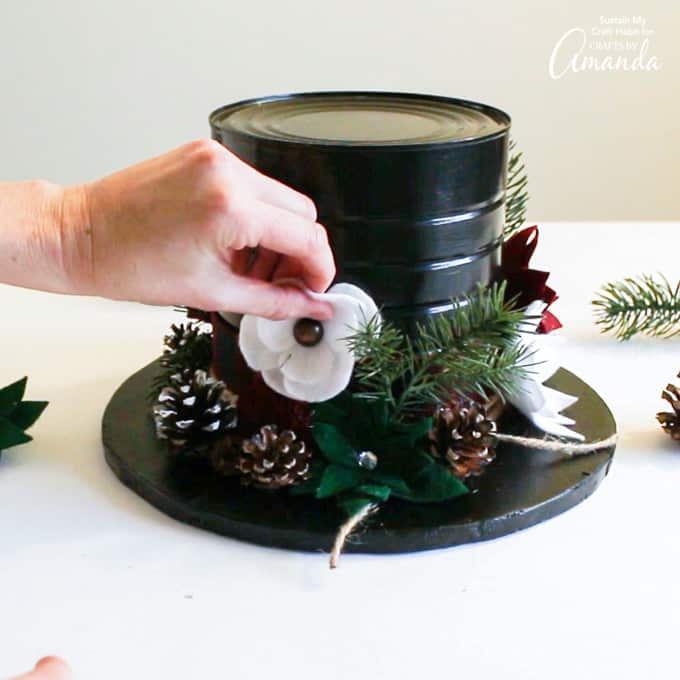 Adding felt flowers and greenery to snowman hat centerpiece