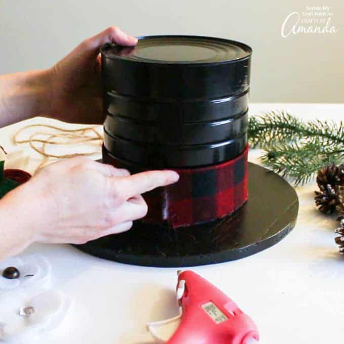 Gluing on cut ribbon to the base of snowman hat centerpiece