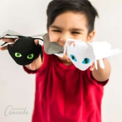 boy holding dragon finger puppets