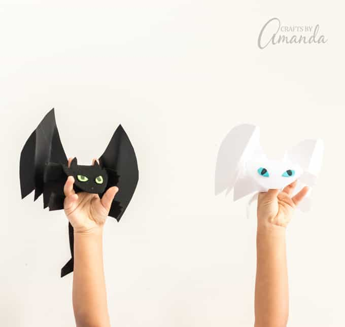 hands holding dragon finger puppets
