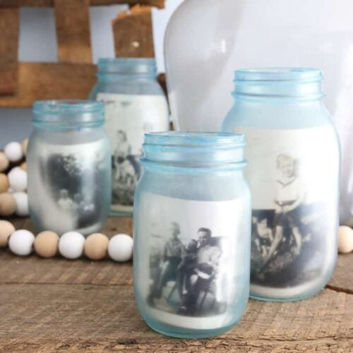 Blue tinted mason jars holding black and white vintage photos