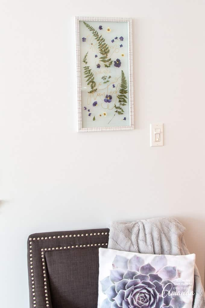 pressed flower art on wall above sofa chair