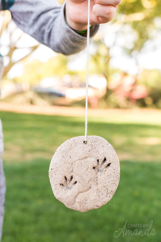 child holding a coffee ground fossil ornament on a string
