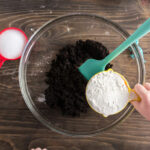 child holding measuring cup of flour over coffee grounds in a bowl