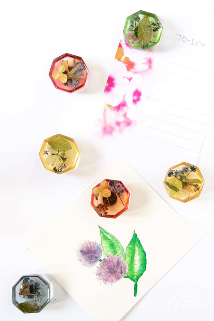 Resin magnets with pressed flowers on fridge