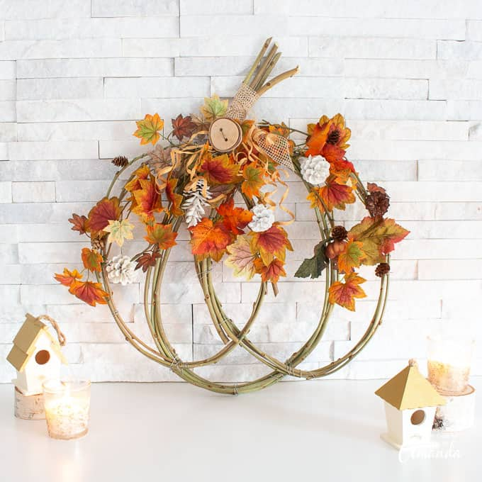 pumpkin grapevine wreath with faux fall foliage and pinecones