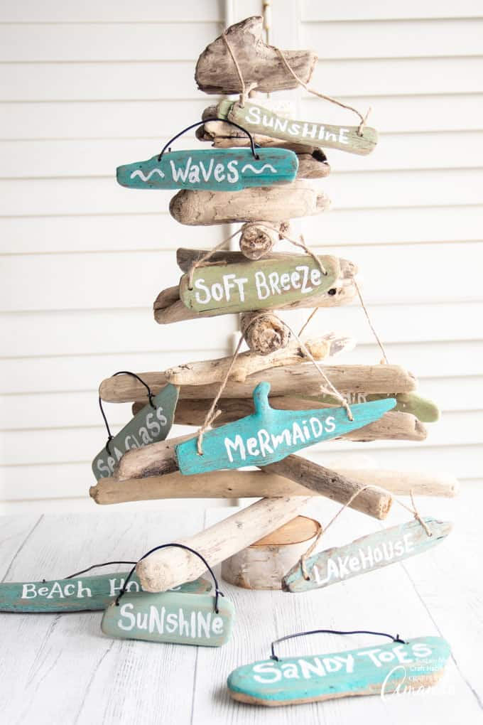 beach sign ornaments with phrases hanging on driftwood tree